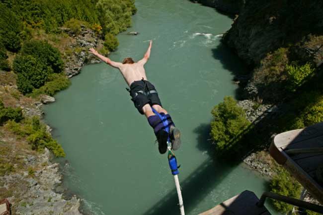 एक ऊंची चट्टान से नदी में डुबकी मारना