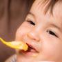 A cute baby is having spoonful of food