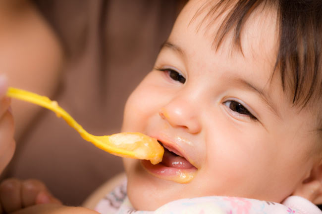 A cute baby is having spoonful of food